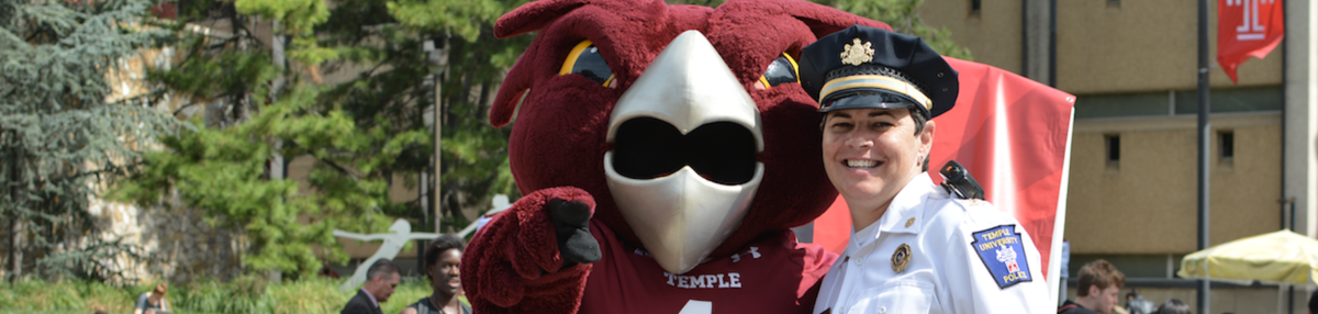 Temple's mascot, Hooter the Owl, standing next to police officer