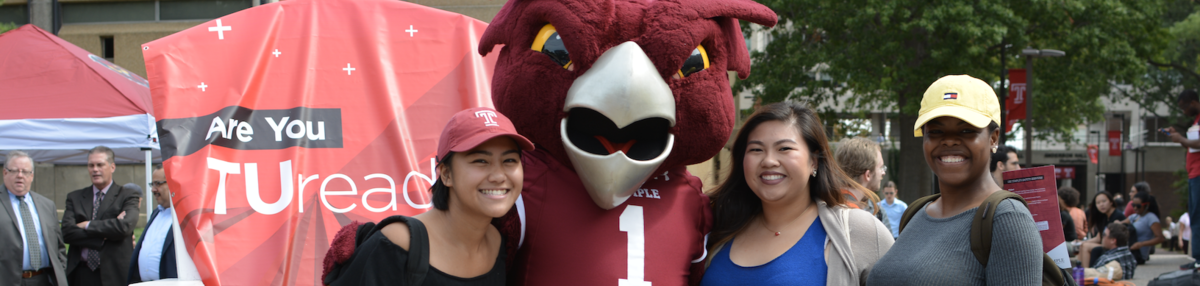 Temple's mascot, Hooter the Owl, standing next to 3 people